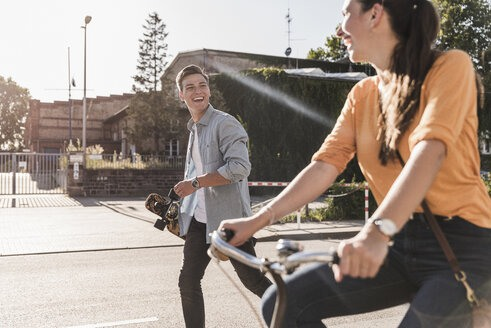 cheerful-young-man-looking-at-girlfriend-riding-bicycle-on-street-in-city-during-sunny-day-UUF20874